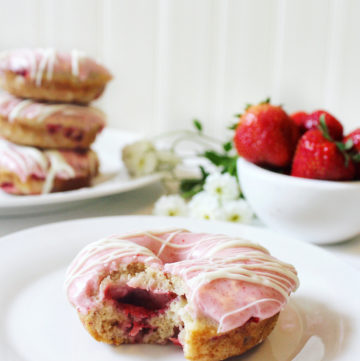 Strawberry donuts, pink frosting, bowl of strawberries