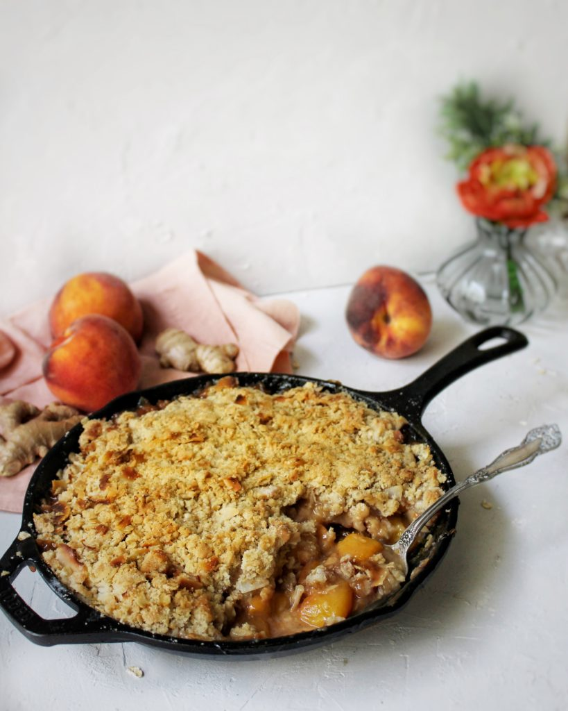 Ginger peach crisp in a cast iron skillet surrounded by peaches and flowers