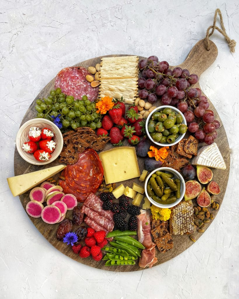 Charcuterie board with cheeses, meats, veggies, fruits