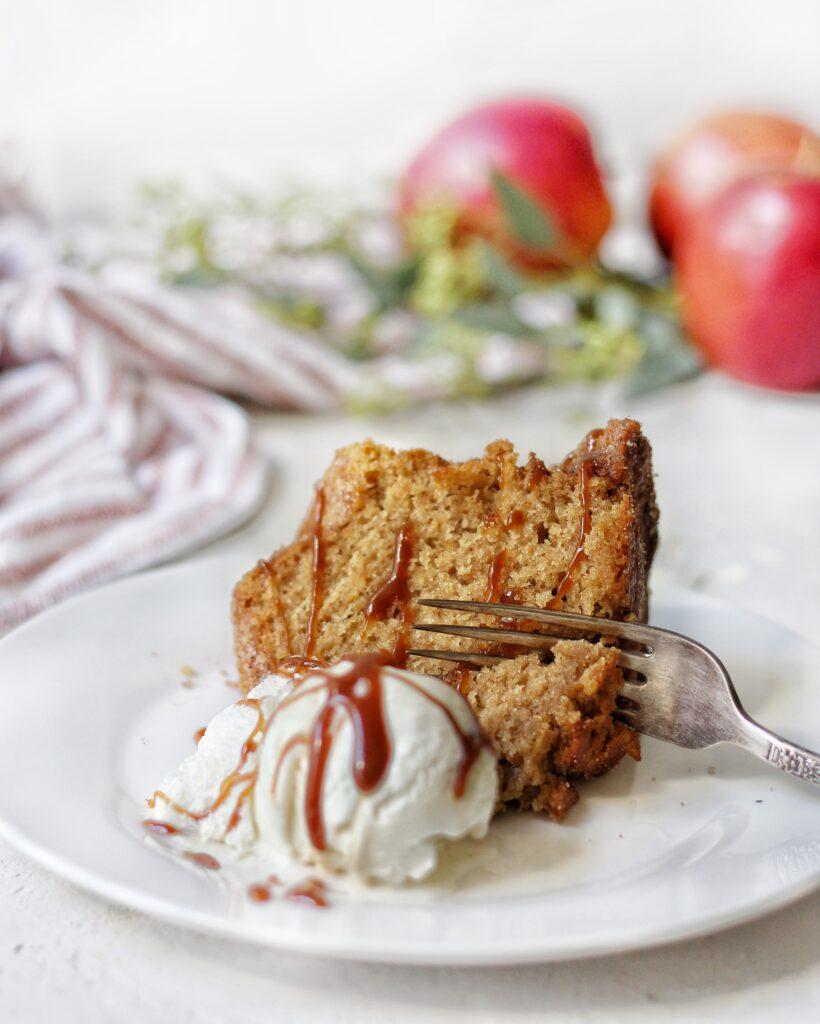 Slice of apple cider donut cake with apple cider caramel and ice cream