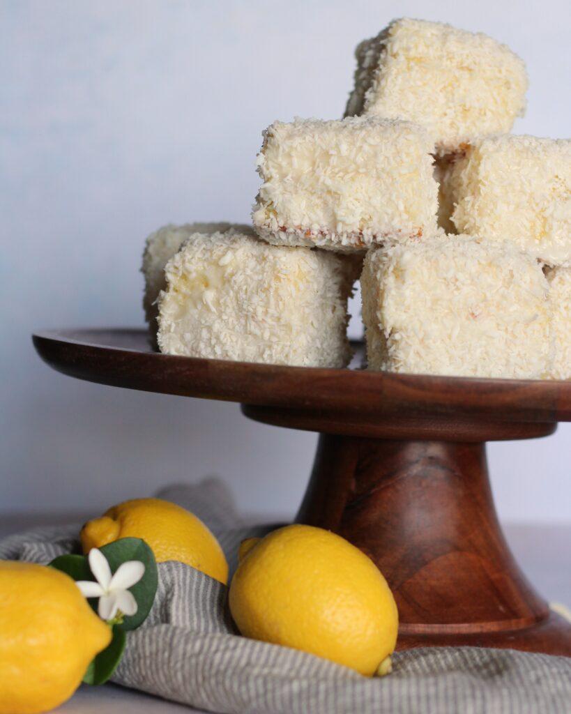 Pile of lemon white chocolate lamingtons on a cake stand with lemons.