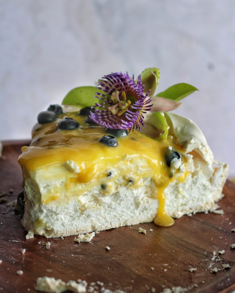 Slice of pavlova cake with passion fruit curd