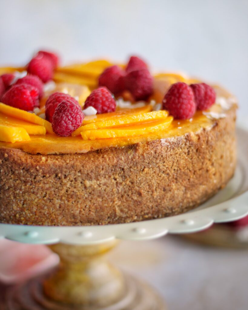close up of mango coconut cheesecake showing detail of coconut graham cracker crust