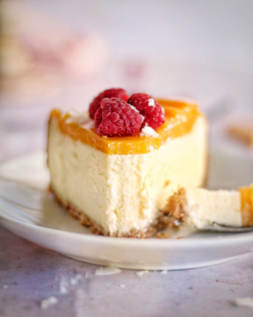 A zoomed in shot of a slice of mango coconut cheesecake